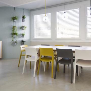 Küche mit grossem Tisch und Sessel, an der Wand hängen Pflanzen